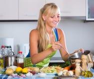 Blondie som förbereder veggies i kök Royaltyfri Foto