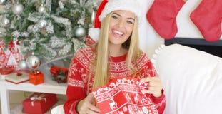 Blondie sorridente grazioso che guarda dentro il suo regalo di natale Fotografie Stock
