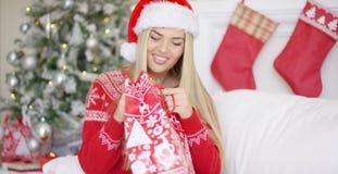 Blondie sorridente grazioso che guarda dentro il suo regalo di natale Fotografia Stock Libera da Diritti