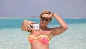 Blondie woman is making selfie on the beach Royalty Free Stock Image