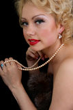 Blondie woman with pearl necklace in hand Stock Photography