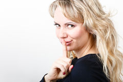 Blondie woman with silence gesture Stock Photography