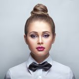 Blondie woman in white shirt and black bow-tie. Young blondie woman in white shirt and black bow-tie over white Stock Images
