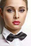 Blondie woman in white shirt and black bow-tie Stock Photography