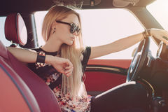 Blondie young girl at the wheel of sport car. With red interior with black sunglasses and black leather armlets with metal inserts seating sideward and looking Stock Photography