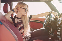Blondie young girl at the wheel of sport car. With red interior with black sunglasses and leather armlets with metal inserts, seating sideward with hand near Stock Image