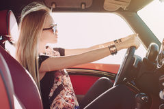 Blondie young girl at the wheel of sport car. With red interior with black sunglasses and leather armlets with metal inserts, seating sideward with two hands on Stock Photos