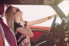Blondie young girl at the wheel of sport car. With red interior with black sunglasses and leather armlets seating sideward with hand near her check and wind in Royalty Free Stock Photo