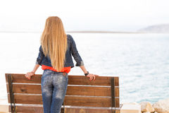 Blondie young woman back view, sea beach bench. Blondie young woman standing bench sea beach, back view, wearing jeans, long hair. Dead sea, Israel Stock Photo