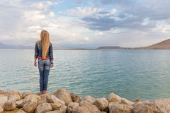 Blondie young woman back view, sea beach stones. Blondie young woman standing stones sea beach, back view, wearing jeans, long hair. Dead sea, Israel Royalty Free Stock Photos