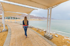 Blondie young woman back view, seafront embankment walking. Blondie young woman swalking embankment sea beach, back view, wearing jeans, long hair. Dead sea Royalty Free Stock Photos