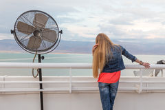 Blondie young woman posing balcony ventilator sea view. Blondie young woman standing balcony sea back view posing wearing jeans, long hair. Dead sea, Israel Stock Image