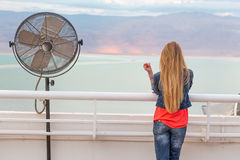 Blondie young woman posing balcony ventilator sea view. Blondie young woman standing balcony sea back view posing wearing jeans, long hair. Dead sea, Israel Stock Photography
