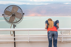 Blondie young woman posing balcony ventilator sea view. Blondie young woman standing balcony sea back view posing wearing jeans, long hair. Dead sea, Israel Royalty Free Stock Image