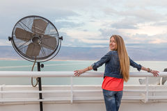 Blondie young woman posing balcony ventilator sea view. Blondie young woman standing balcony sea view posing wearing jeans, long hair. Dead sea, Israel Stock Photo