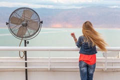 Blondie young woman wind posing balcony ventilator sea view. Blondie young woman standing balcony sea back view posing wearing jeans, long hair. Dead sea Royalty Free Stock Image