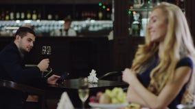 Blondiemeisje die de mens in restaurant van een andere plaats bekijken stock footage