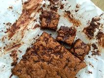 Blondies flourless faits maison de beurre d'écrou avec du chocolat sur le papier parcheminé Photographie stock libre de droits