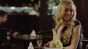 Blondieschoonheid die een mens in restaurant van een andere lijst kijken stock footage