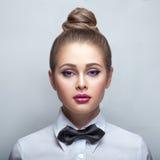 Blondievrouw in wit overhemd en zwarte vlinderdas Stock Afbeeldingen
