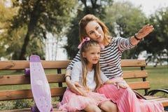 Blondin-haired att bry sig moder som visar hennes flicka det trevliga kafét fotografering för bildbyråer