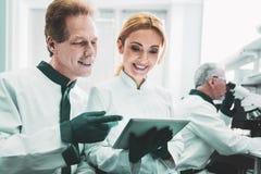 Blondin-haired biolog som ler, medan samarbeta med kollegor royaltyfri bild