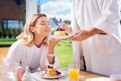 Blondin-haired kvinna som överst luktar trevliga varma pannkakor med frukter royaltyfria foton