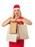 Blondin i jultomten en hjälpredahatt som rymmer en shoppingpåse Royaltyfri Bild