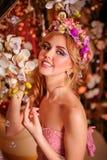 Blondin med blom- i hennes hår och ovanliga smink Royaltyfria Foton