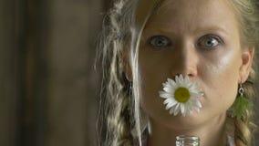 Blondin med en förvånad blick som rymmer en tusensköna i hennes mun stock video
