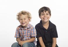 Blondin och bruna haired pojkar som sitter sidan - vid - sida royaltyfria bilder