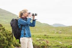 Blondin på en vandring som tar ett foto royaltyfria bilder