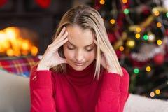 Blondin som får en huvudvärk på juldag Royaltyfri Fotografi