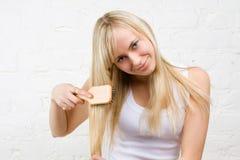 blondin som kammar flickahårbarn Arkivfoto