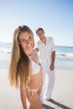 Blondin som ler på kameran med pojkvännen som rymmer hennes hand Royaltyfri Bild