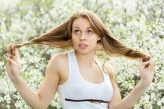 Blondin som spelar med hennes hår Fotografering för Bildbyråer