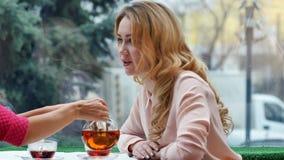 Blondin som tycker om varmt te och samtal med vännen i kafé Arkivfoto