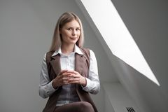 Blonde girl in a business suit works on a computer in a white bright office. royalty free stock images