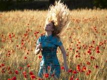 Blondine auf dem Mohnblumegebiet Stockfotos