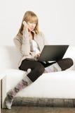 Blondine auf Sofa mit Laptop und Mobiltelefon Lizenzfreie Stockfotos