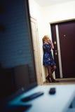 Blondine beantworten Wechselsprechanlagenanruf, halten das Telefon zu seinem Ohr stockbild