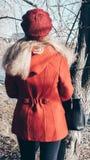 Blondine in den roten Mantel- und Barettst?nden mit seinem zur?ck zu Natur stockfotos