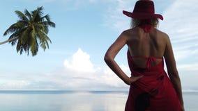Blondine in den roten Sarongen auf einem Ufer stock video