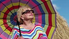 Blondine in den Sonnenbrillen mit viel-farbigen Schirmständern nähern sich Heuschober stock video footage