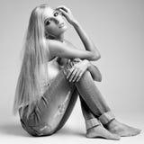 Blondine in den zackigen Jeans und in der Weste Stockfotografie