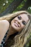 Blondine der jungen Frau auf Bäumen eines Hintergrundes in einem Park Stockbild