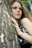 Blondine der jungen Frau auf Bäumen eines Hintergrundes in einem Park Stockfotografie
