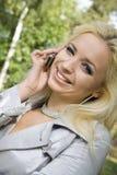 Blondine der jungen Frau auf Bäumen eines Hintergrundes in einem Park Lizenzfreies Stockbild