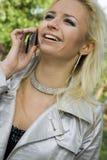 Blondine der jungen Frau auf Bäumen eines Hintergrundes in einem Park Lizenzfreie Stockfotografie