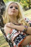 Blondine der jungen Frau auf Bäumen eines Hintergrundes in einem Park Stockbilder